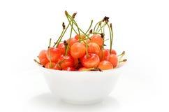 Cerejas maduras em uma placa branca em um fundo branco Imagens de Stock