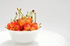 Cerejas maduras em uma placa branca em um fundo branco A bacia da porcelana encheu-se com o fruto, ainda vida Fotos de Stock