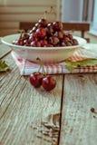 Cerejas maduras frescas em uma placa de madeira escura Tonificação no vintage Imagens de Stock