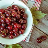 Cerejas maduras frescas em uma placa de madeira escura Tonificação no vintage Foto de Stock