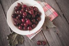 Cerejas maduras frescas em uma placa de madeira escura Tonificação no vintage Foto de Stock Royalty Free