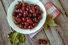 Cerejas maduras frescas em uma placa de madeira escura Tonificação no vintage Fotos de Stock