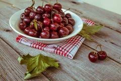 Cerejas maduras frescas em uma placa de madeira escura Tonificação no vintage Fotografia de Stock