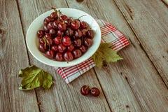 Cerejas maduras frescas em uma placa de madeira escura Tonificação no vintage Fotos de Stock Royalty Free