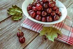 Cerejas maduras frescas em uma placa de madeira escura Tonificação no vintage Imagens de Stock Royalty Free