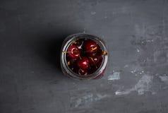 Cerejas maduras no frasco Fotografia de Stock