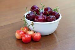 Cerejas maduras vermelhas e cerejas mais chuvosas na tabela fotografia de stock