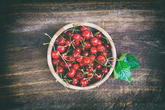 Cerejas maduras vermelhas em uma bacia de madeira em uma tabela velha Imagens de Stock