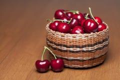Cerejas maduras vermelhas em uma cesta em uma tabela de madeira fotografia de stock royalty free