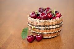 Cerejas maduras vermelhas em uma cesta em uma tabela de madeira fotos de stock royalty free