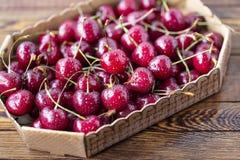 Cerejas maduras vermelhas, cerejas vermelhas na tabela de madeira, fundo de madeira marrom Fotografia de Stock Royalty Free