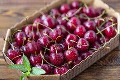 Cerejas maduras vermelhas, cerejas vermelhas na tabela de madeira, fundo de madeira marrom Fotos de Stock