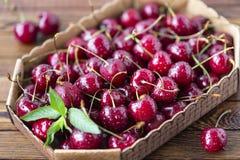 Cerejas maduras vermelhas, cerejas vermelhas na tabela de madeira, fundo de madeira marrom Imagem de Stock