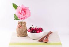 Cerejas na bacia branca e na colher de madeira com as flores em b branco Imagens de Stock