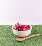 Cerejas na bacia branca e na colher de madeira na grama verde com whi Foto de Stock