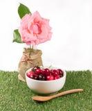 Cerejas na bacia branca e na colher de madeira no gramado e na flor verdes Imagens de Stock Royalty Free