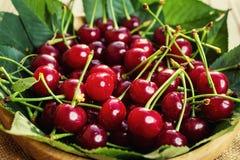 Cerejas na cesta na tabela de madeira Cereja Cerejas na bacia Cereja vermelha Cerejas doces frescas com gotas da água, fim acima  Fotos de Stock