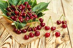 Cerejas na cesta na tabela de madeira Cereja Cerejas na bacia Cereja vermelha Cerejas doces frescas com gotas da água, fim acima  Foto de Stock
