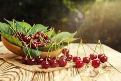 Cerejas na cesta na tabela de madeira Cereja Cerejas na bacia Vermelho Fotos de Stock