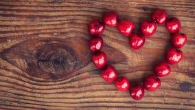 Cerejas no fundo de madeira na forma do coração Fotos de Stock Royalty Free