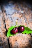 Cerejas no fundo de madeira rústico Fotografia de Stock Royalty Free
