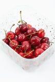 Cerejas no recipiente plástico no fundo branco Imagens de Stock