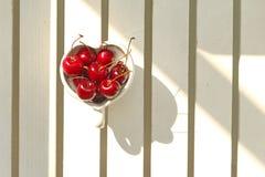 Cerejas o Chile na caneca Coração-dada forma na madeira Fotografia de Stock