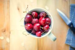 Cerejas orgânicas cruas frescas em um copo Imagens de Stock