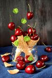 Cerejas que caem em cones do waffle foto de stock