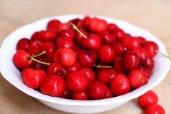 Cerejas saudáveis, suculentas, frescas, orgânicas no fim da bacia de fruto acima Cerejas no fundo Imagens de Stock