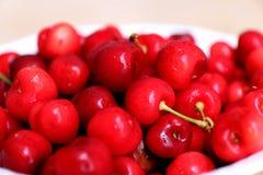 Cerejas saudáveis, suculentas, frescas, orgânicas no fim da bacia de fruto acima Cerejas no fundo Fotos de Stock Royalty Free