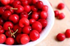 Cerejas saudáveis, suculentas, frescas, orgânicas no fim da bacia de fruto acima Cerejas no fundo Foto de Stock Royalty Free