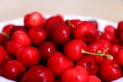 Cerejas saudáveis, suculentas, frescas, orgânicas no fim da bacia de fruto acima Cerejas no fundo Fotografia de Stock