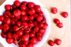 Cerejas saudáveis, suculentas, frescas, orgânicas no fim da bacia de fruto acima Cerejas no fundo Fotografia de Stock Royalty Free