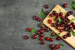 Cerejas vermelhas doces na placa de madeira fotografia de stock