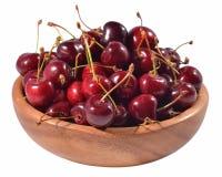 Cerejas vermelhas em uma bacia de madeira em um branco fotos de stock royalty free