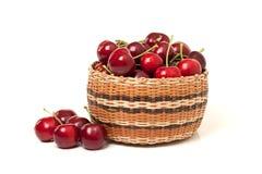 Cerejas vermelhas em uma cesta no fundo branco Fotos de Stock