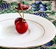 Cerejas vermelhas em uma placa branca Fotografia de Stock