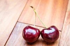 Cerejas vermelhas frescas em uma tabela de madeira Fotos de Stock