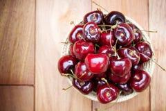 Cerejas vermelhas frescas em uma tabela de madeira Foto de Stock Royalty Free