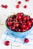 Cerejas vermelhas na bacia no fundo de madeira branco na toalha azul Foto de Stock Royalty Free