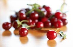 Cerejas vermelhas na tabela de madeira Imagens de Stock Royalty Free