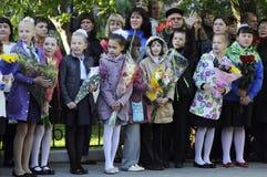 1 ceremoni blommar elever september En högtidlig linjal av elever i skolgården Arkivfoto