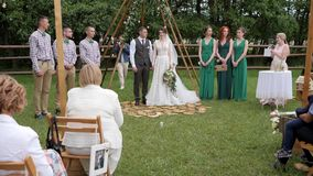 Ceremonia de boda en naturaleza, recienes casados y huéspedes en el aire libre nupcial, novia feliz y novio con sus testigos