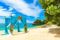 Ceremonia de boda en una playa tropical en azul El arco adornó ingenio Fotografía de archivo libre de regalías