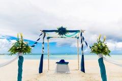 Ceremonia de boda en una playa tropical en azul El arco adornó ingenio Foto de archivo libre de regalías