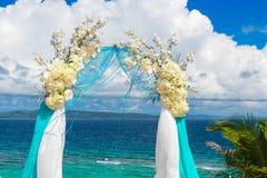 Ceremonia de boda en una playa tropical en azul El arco adornó ingenio Fotos de archivo