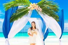 Ceremonia de boda en una playa tropical en azul Novia feliz debajo Imagen de archivo libre de regalías