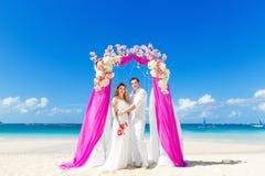 Ceremonia de boda en una playa tropical en púrpura Novio feliz y Fotografía de archivo