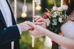 Ceremonia de boda La novia pone un anillo de bodas al novio en un fondo de las bombillas que sostienen un ramo en sus manos fotografía de archivo